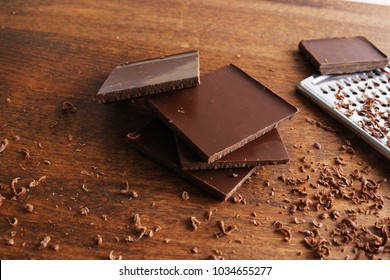 grated chocolate on a wooden background grater