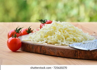 Grated mozzarella cheese and cherry tomatoes on wooden table, shallow dof