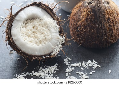 Grated organic coconut in a half fresh coconut.