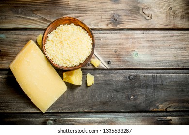 Grated Parmesan cheese in bowl. On a wooden background.