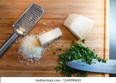 grated parmesan cheese, chopped basil, knife and metal grater on wooden plate