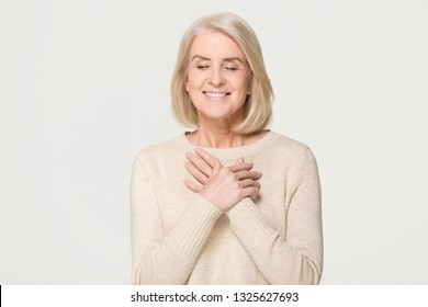 Grateful happy mature old woman holding hands on chest feeling hopeful thanking for honesty love sincere appreciation, touched pleased middle aged senior lady isolated on white grey studio background