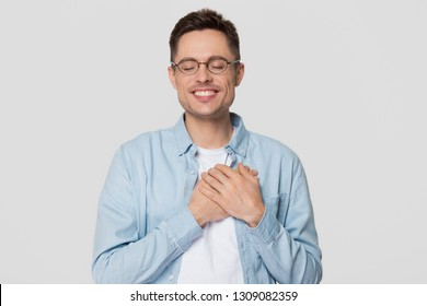 Grateful happy young man in glasses holding hands on chest close to heart feeling appreciation honesty sincere love, thankful guy proud touched pleased isolated on white grey studio blank background