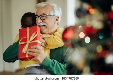 Grateful little girl embracing her grandfather while receiving Christmas present at home. Focus is on man.