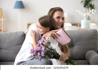 Grateful loving young mom thanking embracing little cute daughter holding gift box and flowers bouquet, kid girl hugging happy mommy congratulating mum with birthday or mothers day making present