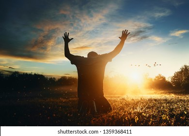 Grateful man man raising his hands in worship in the countryside.