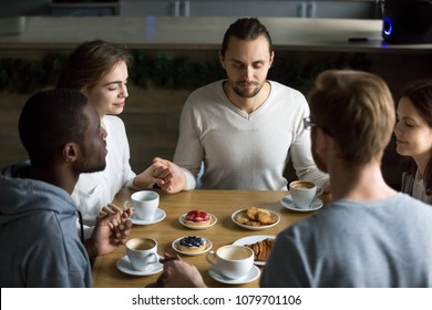 Grateful multiracial young friends holding hands sitting at home or cafeteria table saying grace concept, religious people blessing food praying meditating thanking before eating breakfast together