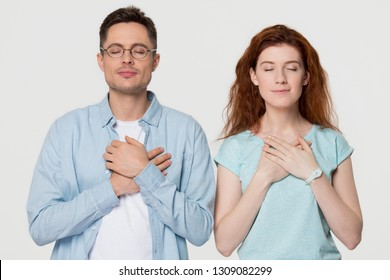 Grateful thankful young couple holding hands on chest feel heartfelt appreciation, sincere love, faith and honesty, happy pleased touched man and woman isolated on white grey studio blank background