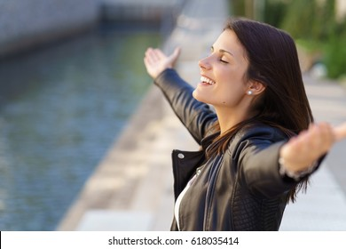 Grateful woman with eyes closed and arms extended standing near stone walkway and small canal