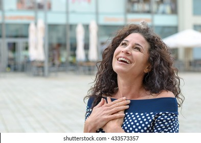 Grateful young woman with her hands to her heart standing outdoors in an town square smiling up to the sky in gratitude