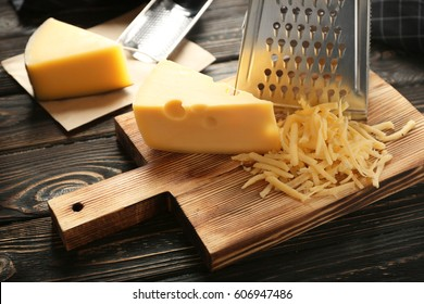 Grater and cheese on wooden board