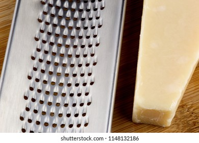 Grater and parmesan cheese on a wooden table