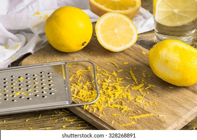 Grater peel and lemon zest on the wooden table