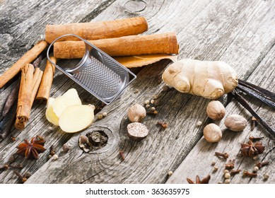 grater with sliced ginger root, cinnamon, vanilla, nutmeg and other spices on old wood table