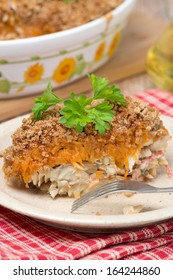 Gratin with fish and pumpkin on a plate, vertical, close-up