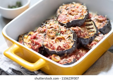 Gratin with grilled eggplant, tomato sauce, olives and cheese