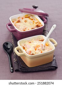 Gratin of rice and ham in a ceramic cocotte on a napkin
