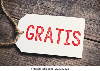Gratis on blank tags. Red inscription Gratis on blank tags on wooden table