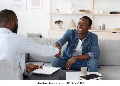 Gratittude For Work. Black Man Handshaking With Psychologist After Therapy Session Meeting, Sitting On Couch At His Office