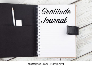 Gratitude Journal on white wood desk with space for text