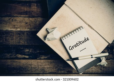 Gratitude word on pages sketch book on wood table vertical