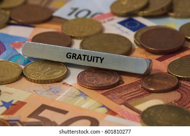 gratuity - the word was printed on a metal bar. the metal bar was placed on several banknotes