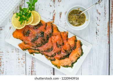 Gravadlax - Nordic dish of thinly sliced raw salmon cured in salt, sugar and dill and accompanied by dill and mustard sauce - top view