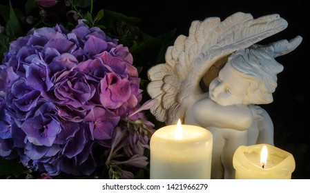 Grave with angel, grave light and flowers,