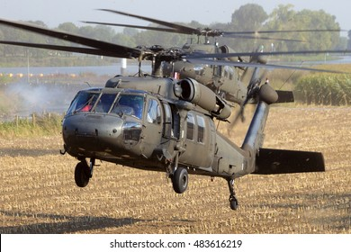 GRAVE, NETHERLANDS - SEP 17, 2014: Two American Army Blackhawk helicopter landing in a field.