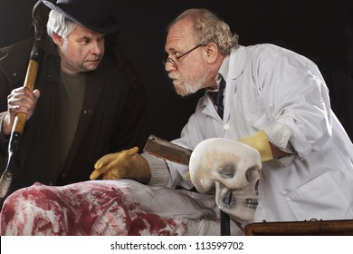 Grave robber and evil doctor with bloody cleaver exchange conspiratorial glances. Stage effect, isolated on black background, spot lighting.
