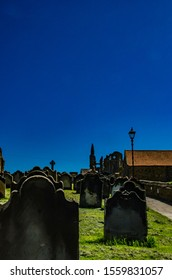 Grave stones against dark blue background. Copy space at the top and room to add inscriptions on stones.