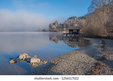 gravel beach at lake schliersee with boathouse and morning fog. upper bavaria.