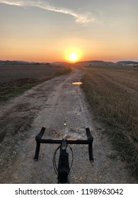 Gravel bike on dirt country road at summer sunset