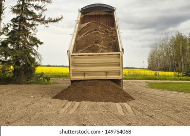 A gravel box tilted up dumping a load of gravel