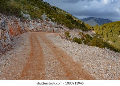 Gravel mountain road scene in the afternoon against a cloudy sky in mountain range of Taigetos in Greece