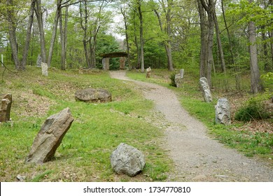A gravel path in a wooded area that leads to a stone arch.  Besides the path is a grass area with several large boulders.