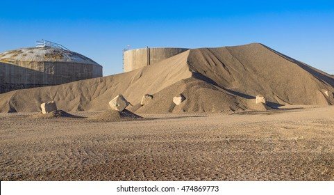 Gravel Pit with Cement Blocks, Storage Silos and Blue Sky.