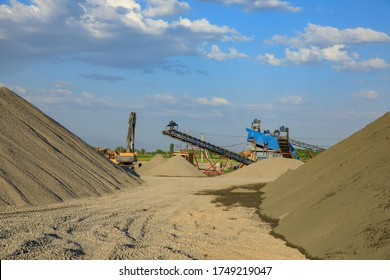Gravel pit excavation site on a sunny day with industrial machines