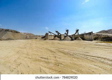 Gravel pit excavation site on a sunny day with industrial machines.