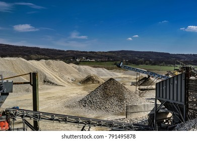 Gravel pit with heavy machineries with blue sky and white clouds on a sunny day.