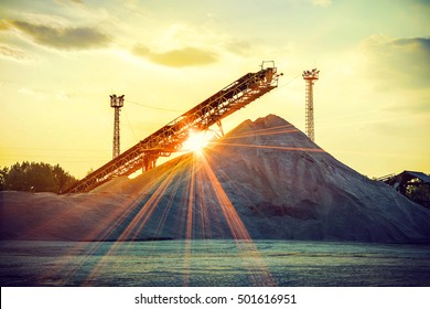 gravel pit with an industrial gravel sorter machinery at sunset
