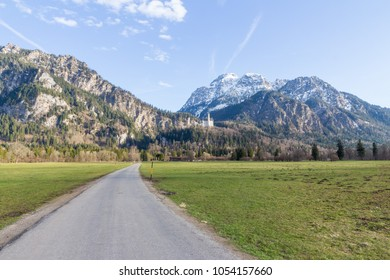 Gravel road along fields in the Allgau region, Bavaria, Germany, leading towards famous Neuschwanstein castle