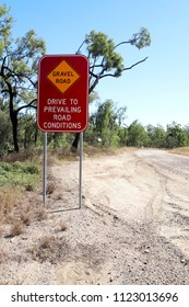 Gravel Road Drive to Prevailing Road Conditions sign on gravel road in Australia.