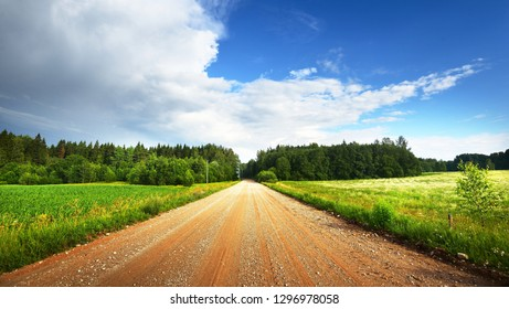 Gravel road going through field and forest in Latvia countryside