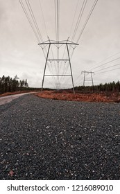 A gravel road leads to the giant pilars holding the power lines at the Northern Finland. The dark skies gather over the towers.
