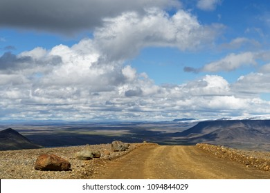 A gravel road leads over a small hill, behind it is a wide landscape with plain, mountain ranges and glaciers to see, above blue sky with white and gray clouds - Location: Iceland, highlands