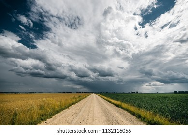 Gravel road in the middle of green and yellow fields and stormy clouds above it