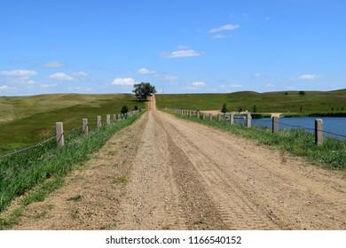 Gravel road over man made dam in Elgin, North Dakota.  Prairie landscape.  Long road. Blue sky and clouds.