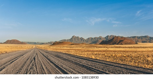 gravel road passing through the steppe and mountains in the background, Africa Namibia.