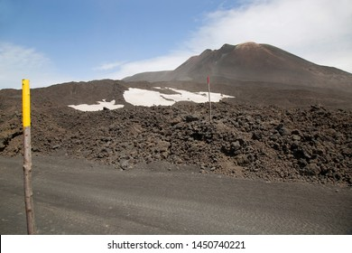 gravel road through lava stones and fields flowing from mount Etna steep slopes marked on both sides with high poles in case of snow covering the road